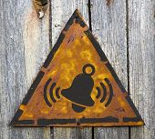 Ringing Bell Icon on Rusty Warning Sign.