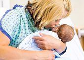 Closeup of loving mother kissing newborn babygirl in hospital