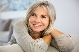 foto of couch  - Smiling senior woman sitting in couch at home - JPG