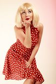 Pinup Girl In Blond Wig Retro Dress Blowing A Kiss