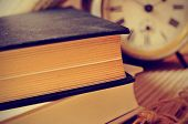 closeup of a pile of old books and an old alarm clock on a desk, with a retro effect