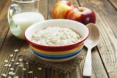 stock photo of oats  - Porridge oats milk and red apples on the table