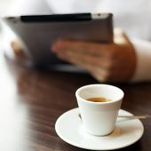 Coffee Cup. Man Reading News On Tablet Computer In Cafe