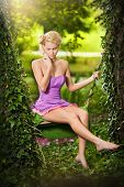 Beautiful young woman in pink short dress dreaming in a leaves decorated swing between two trees