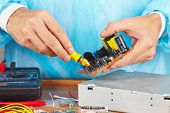 Master parses electronic hardware for repair in service workshop