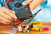 Serviceman checks electronic components of device with multimeter