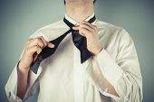 Young Man Tying A Bow Tie