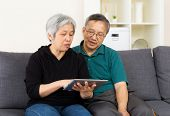 Senior couple with touchpad sitting at home