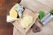 Different Italian cheese on sackcloth, on wooden background