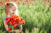 Little girl on the poppy meadow with posy