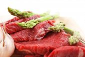 fresh raw beef meat steak fillet on wooden plate with asparagus and tomatoes ready to prepare isolat