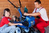 Man And Boy Preparing A Cultivator Machine For Work