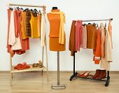 Wardrobe with orange clothes arranged on hangers and an autumn outfit on a mannequin.