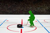 picture of bandy stick  - Toy hockey player and puck in a center of stadium - JPG