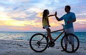 Father and daughter with bike on a beach at sunset