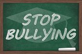stock photo of stop bully  - Stop Bullying Message Stop Bullying written on a chalkboard with chalk and a grad cap - JPG