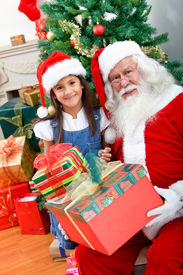stock photo of santa claus hat  - Christmas portrait of a girl with Santa Claus smiling - JPG