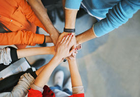 stock photo of bonding  - Top view image of group of young people putting their hands together - JPG