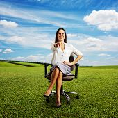 laughing woman sitting on the office chair and pointing at camera. photo on the green meadow over blue sky