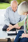 Senior couple playing Rummikub while sitting at nursing home