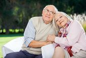 Portrait of loving senior couple sitting on chairs at nursing home porch