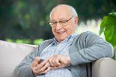 Smiling senior man text messaging through mobile phone at nursing home porch