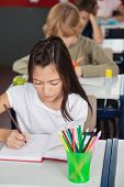 Little schoolgirl writing in book with classmates in background at classroom