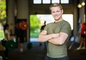Portrait of smiling male athlete standing arms crossed at gym