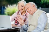 Happy elderly couple video chatting on laptop while sitting at nursing home porch