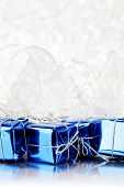 Decorative blue boxes with holiday gifts on shiny glitter background