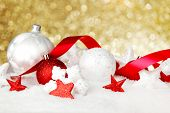 Christmas card with beautiful red and white decorations in snow on golden background