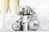 Two champagne glasses and christmas decoration on silver bokeh background
