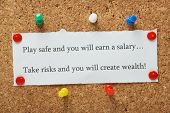 foto of entrepreneur  - Playing it safe versus taking risks concept for entrepreneurs or people in work typed on a piece of paper and pinned to a cork notice board - JPG