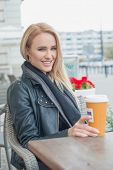 Attractive woman sitting drinking coffee at an outdoor restaurant on a cold day in her warm winter fashion