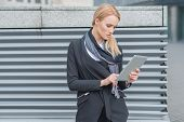 Attractive stylish young blond woman standing using a tablet outdoors in front of a metal louver grating