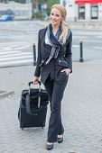 Young businesswoman standing in a stylish outfit in an urban street with a suitcase while on a business trip