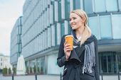 Young Smiling Businesswoman Outside Office Building Holding Cup of Coffee.