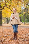 Pretty Young Female in Stylish Autumn Fashion  Standing on Ground full of Dried Leaves while Looking at Camera.