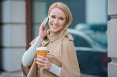 Attractive woman taking a call on her mobile phone smiling as she listens to the conversation with a mug of takeaway coffee in her hand