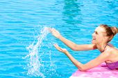 Happy blond woman splashing water in a swimming pool with sparkling turquoise blue water laughing as she throws it up into the air with her hands