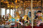 pic of carnival ride  - Brightly painted horses on a vintage carousel or merry - JPG