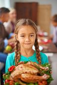 Portrait of cute girl with cooked poultry looking at camera with her family on background