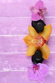 Composition with beautiful blooming orchids and spa stones on color wooden background