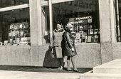 Vintage photo of mother and daughter looking bookshop window, sixties