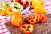 Pepper on plate and on wooden cutting board on fabric background