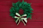 Green Christmas wreath with red and gold bow hanging on dark red wooden background
