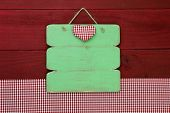 Blank antique green sign with red checkered heart and gingham tablecloth on red wood background