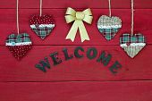 Welcome sign on antique red wood barn door with fabric country hearts and gold Christmas bow