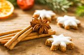 Cinnamon biscuits and christmassy spices on a wooden background