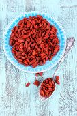 Goji berries on blue plate and in metal spoon on old blue wooden background